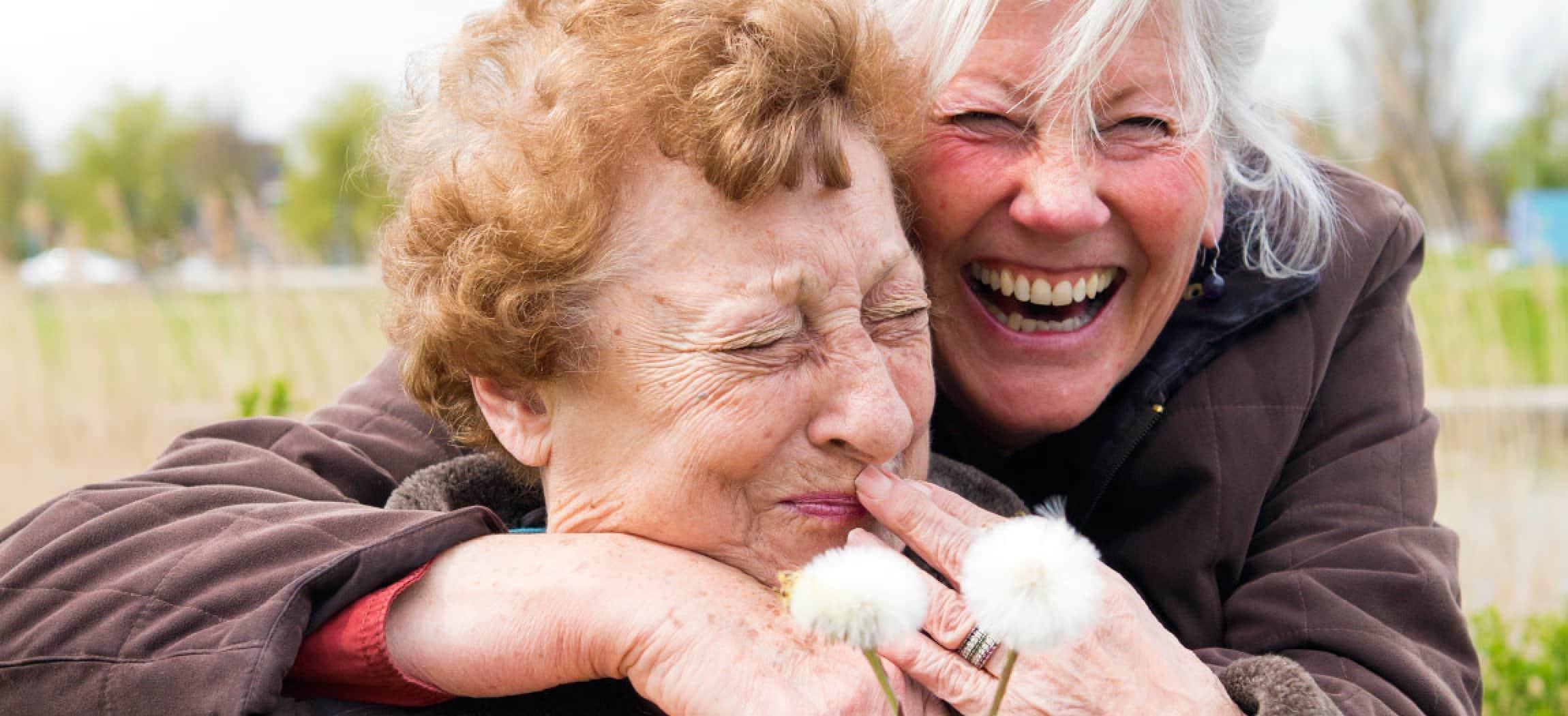 Vrolijk lachende dochter omhelst haar bejaarde moeder, met pluizende paardenbloemen