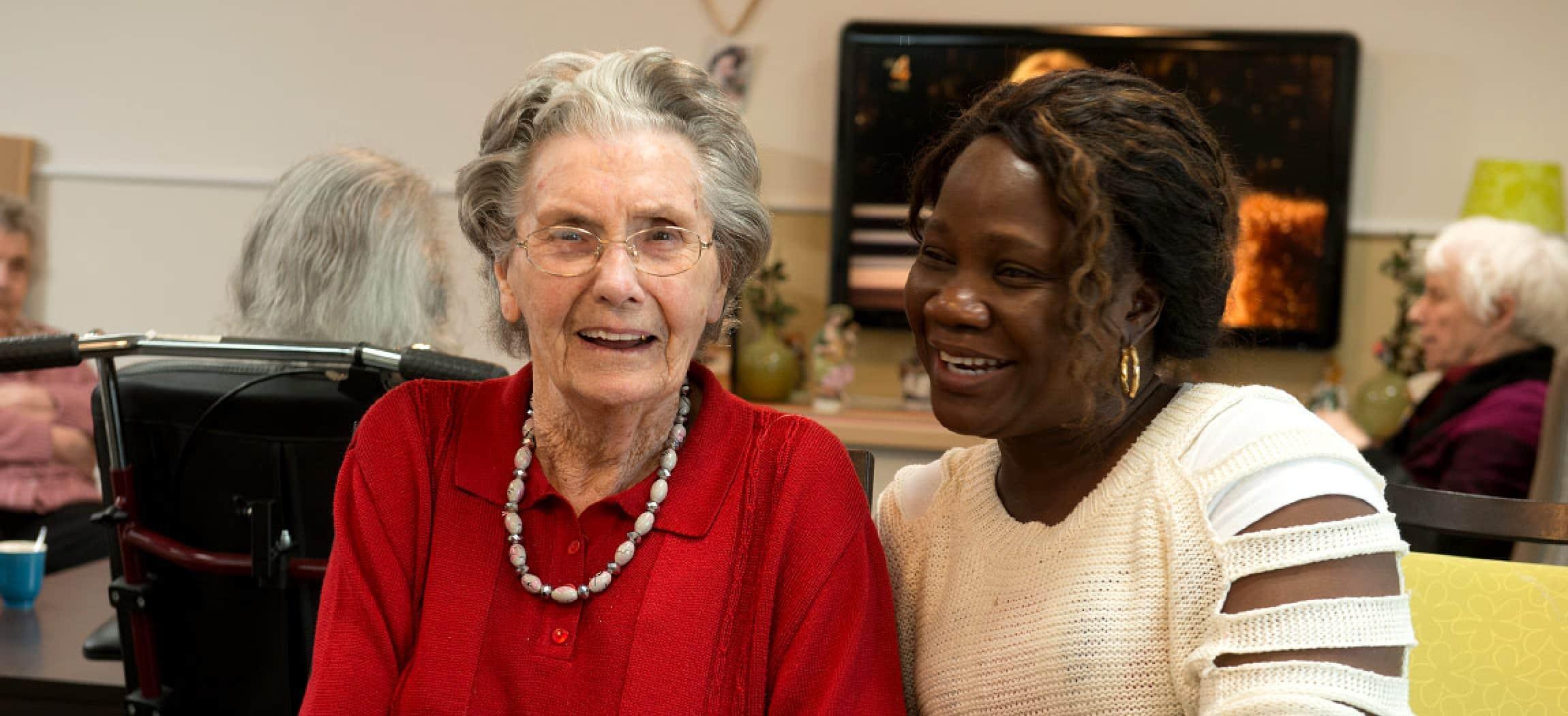 Oudere vrouw met rode trui in verzorgingshuis