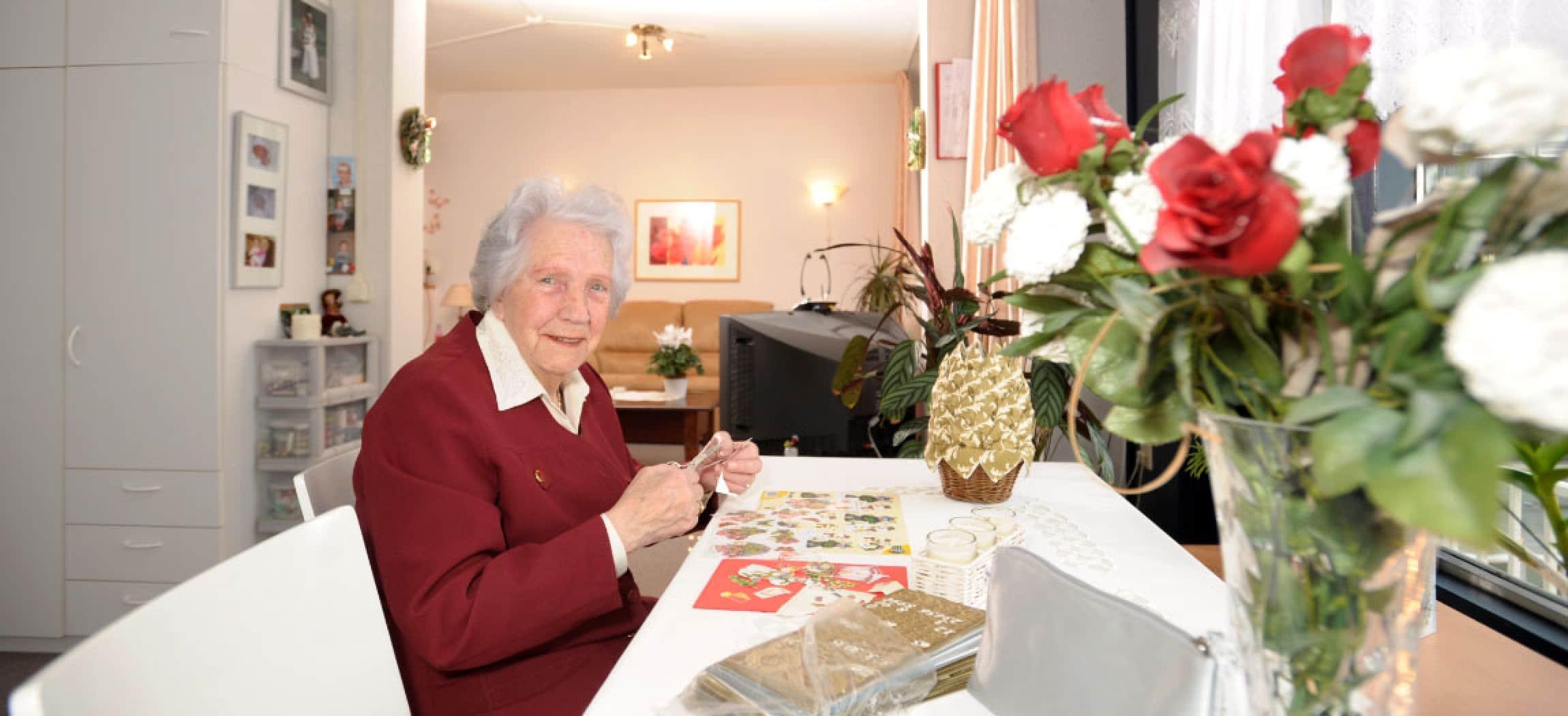 Vrouw met poëzieplaatje, schaar, ansichtkaarten en bos rozen in woonkamer