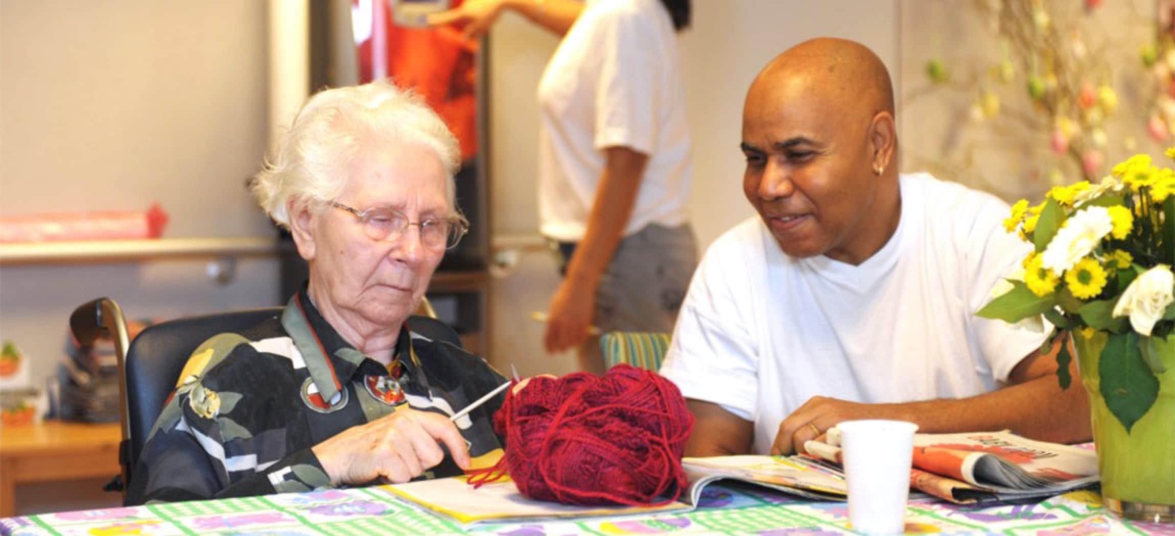 Mannelijke verzorgende kijkt naar oude vrouw met breiwerk en bol wol