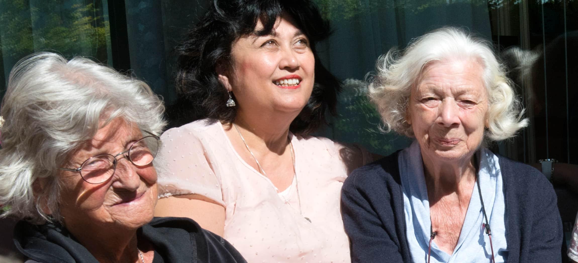 Vrouw met zwart haar en roze blouse zit tussen twee bejaarde dames