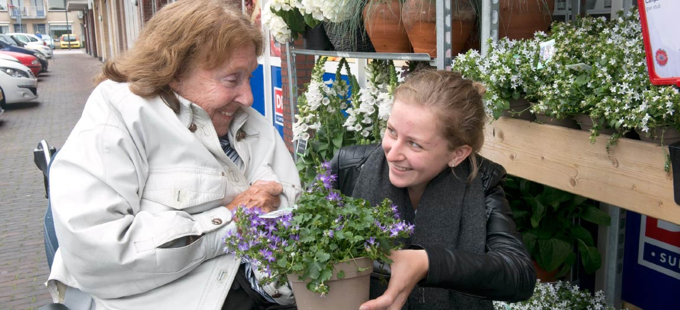 Verzorgster met oudere vrouw in rolstoel bij plantenwinkel