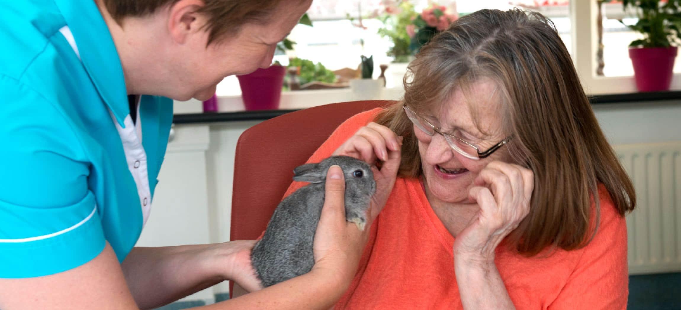 Een huisdier op bezoek bij oudere vrouw in een groepswoning