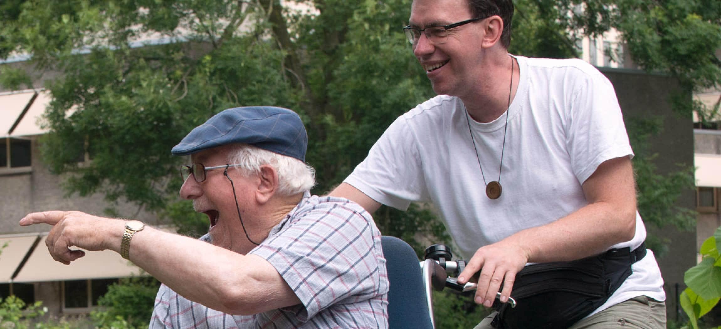 Enthousiaste blije man met klepmuts (ouderwetse pet) op een rolstoeltransportfiets met begeleider