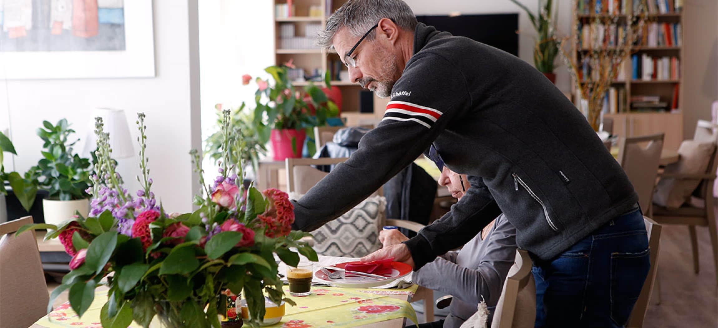 Vrijwilliger man helpt bij ontbijttafel in hospice