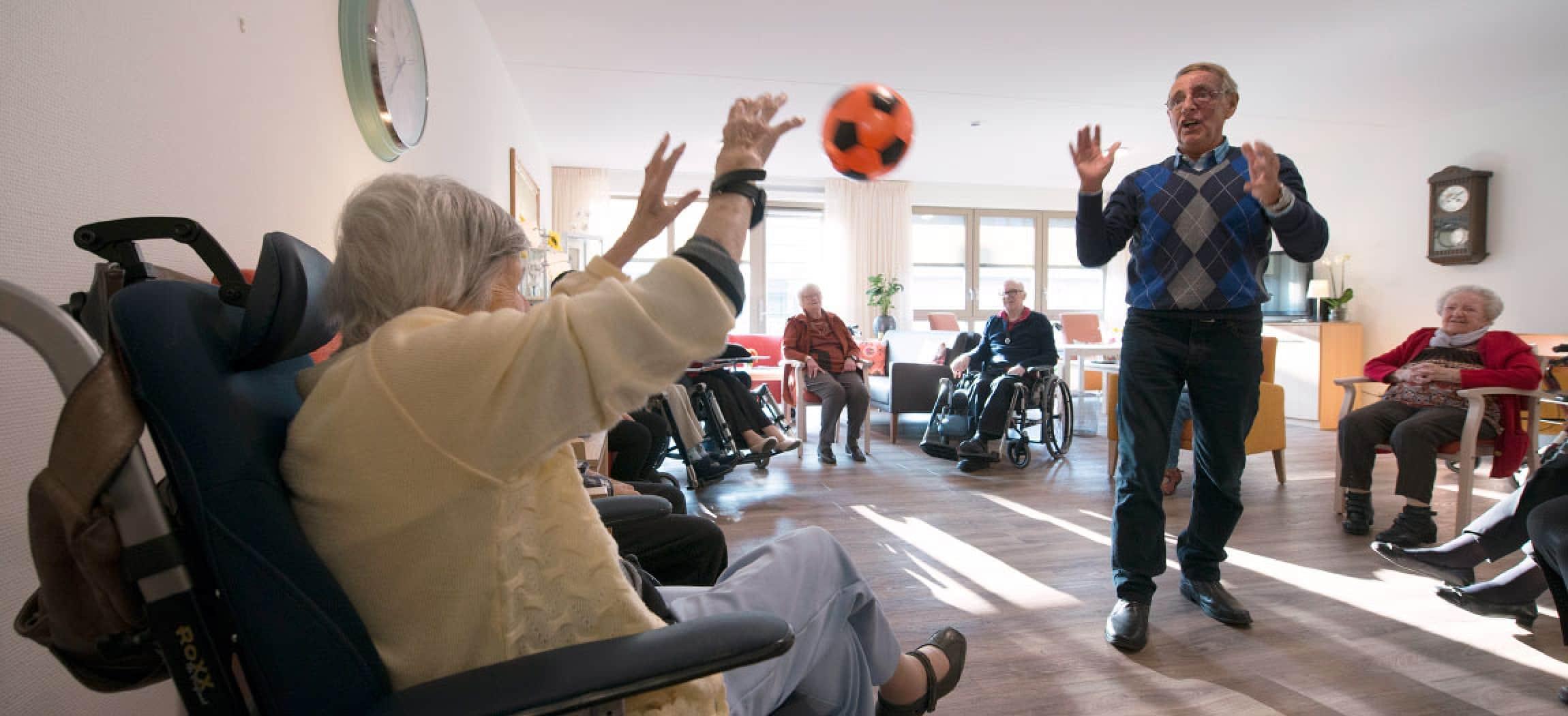 Bewegen voor ouderen in rolstoel gooien met bal