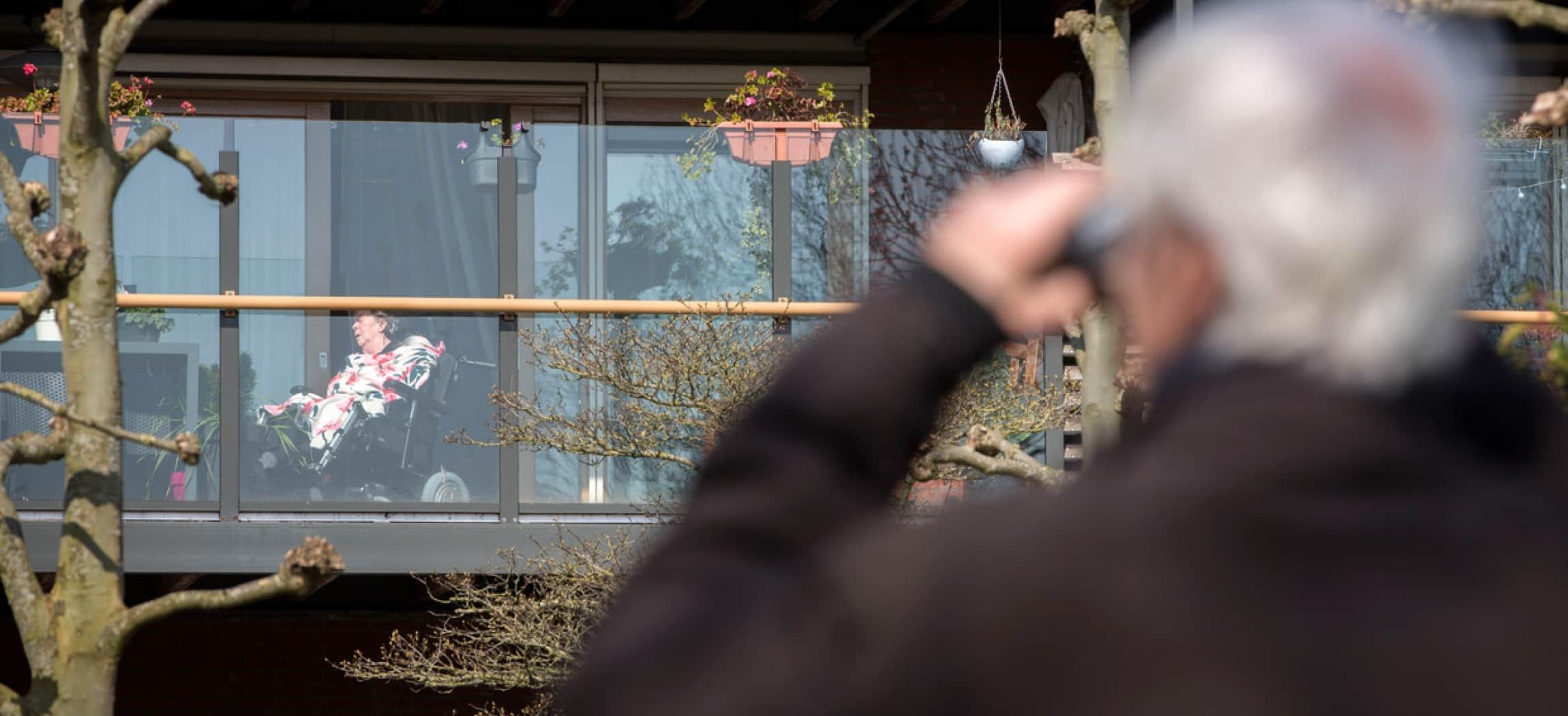 Oudere heer kijkt met verrekijker naar zijn vrouw op het balkon van het verpleeghuis