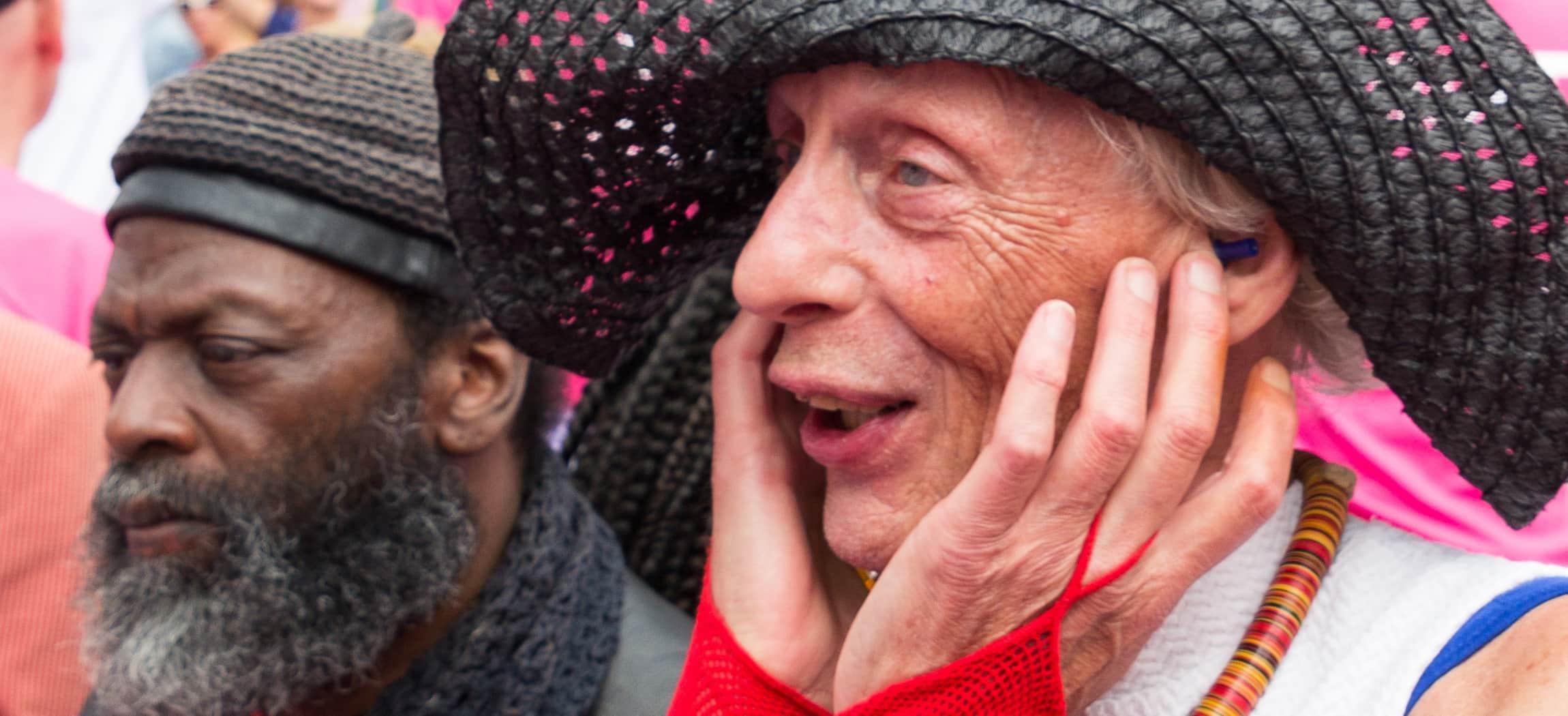 Tijdens Canal Pride kijkt oudere man blij en enthousiast met zwarte flaphoed