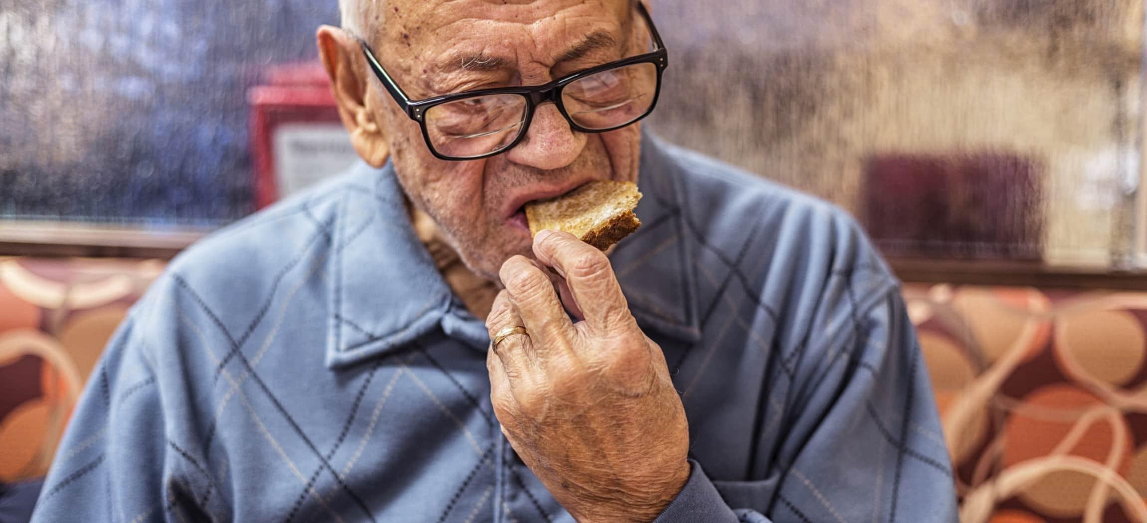 oude man met bril zit op bank en eet een geroosterde boterham met de hand