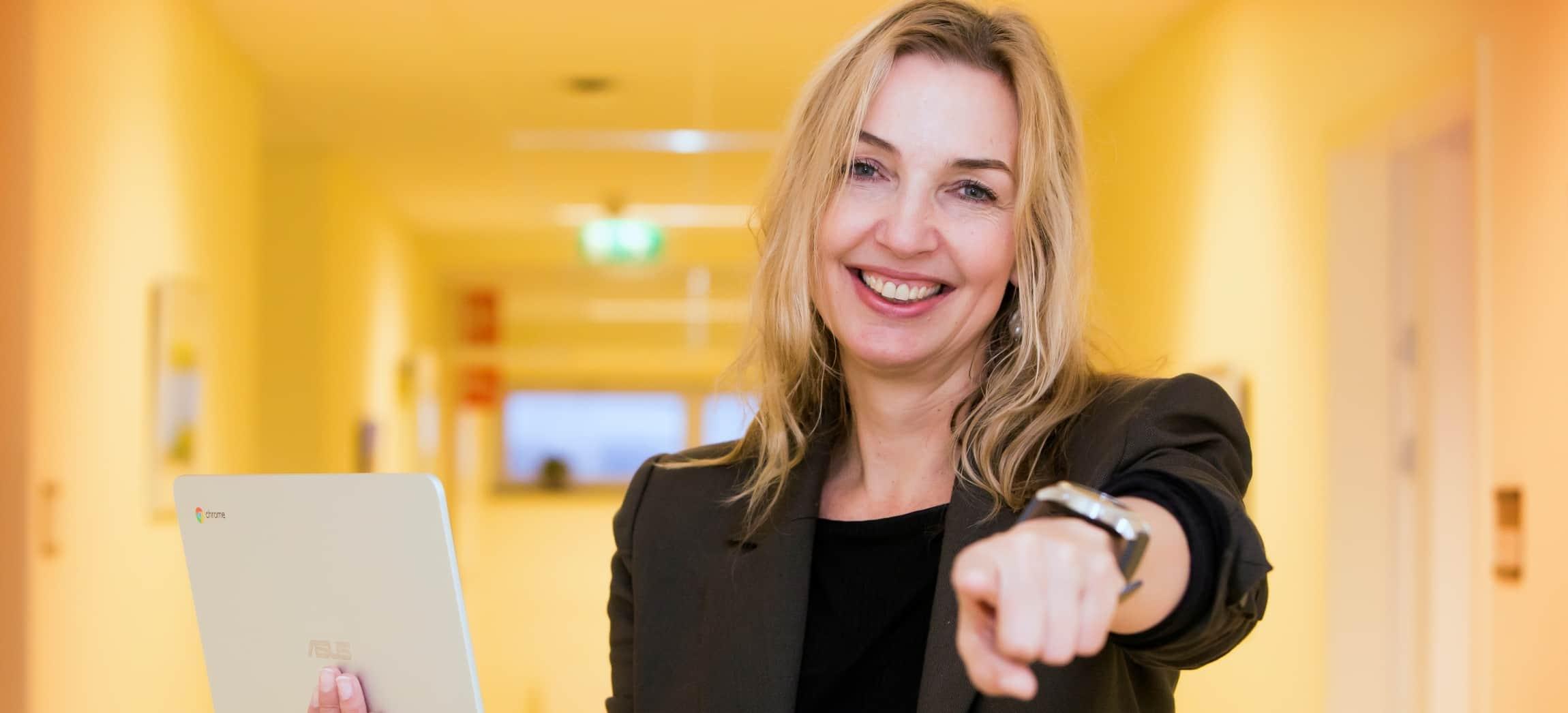 Vrouw met blonde haren in zwart colbertjasje houdt Chromebook vast en wijst naar de camera in gele gang