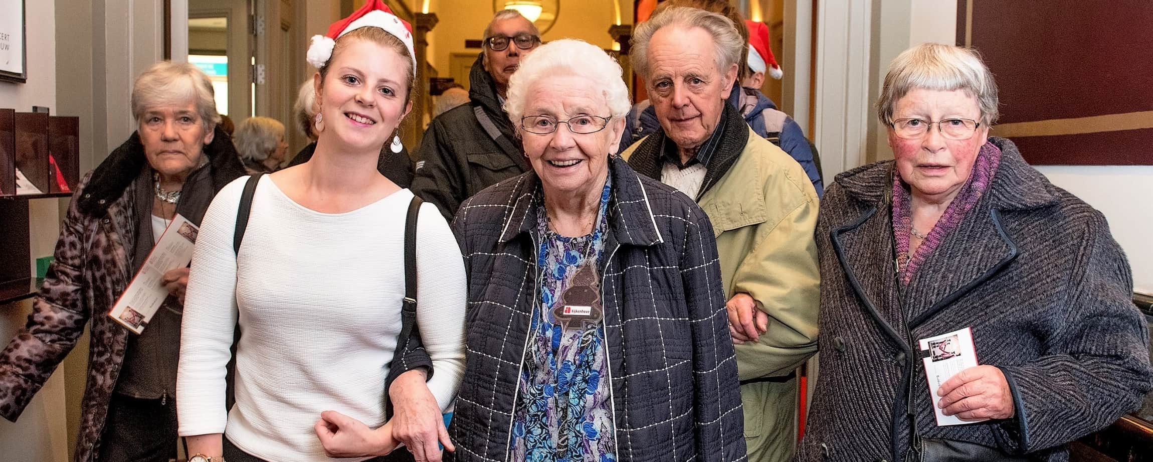 Groep ouderen met jassen aan en een jonge vrijwilliger in Concertgebouw in Amsterdam