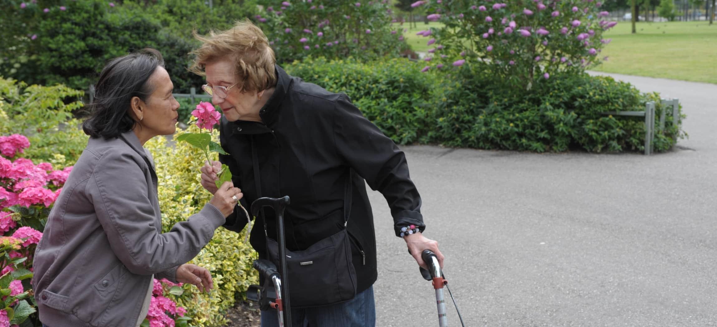 Vrouw met rollator buiten in een park ruikt aan een bloem samen met andere vrouw