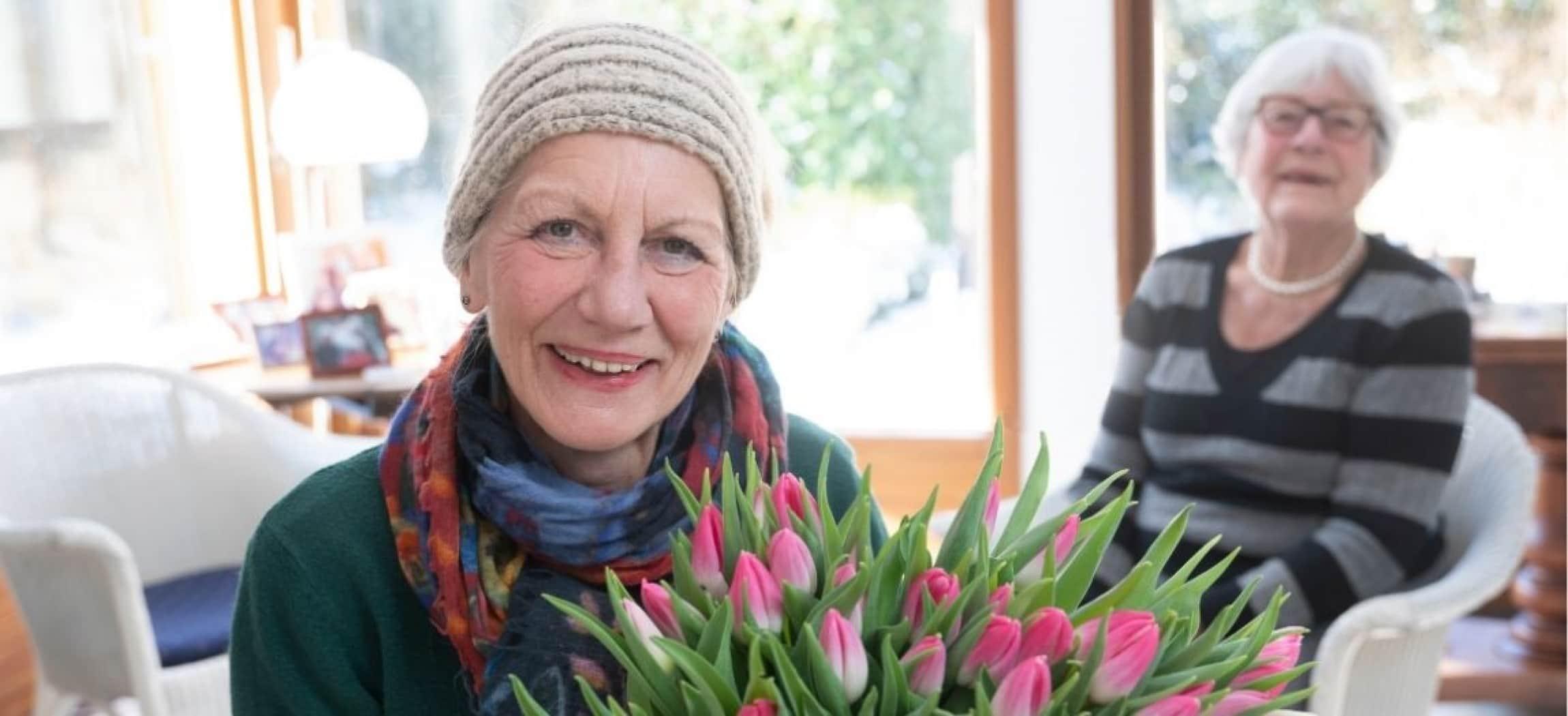 Manja Bunschoten van Amstelring Wijkzorg met een bos tulpen in haar handen