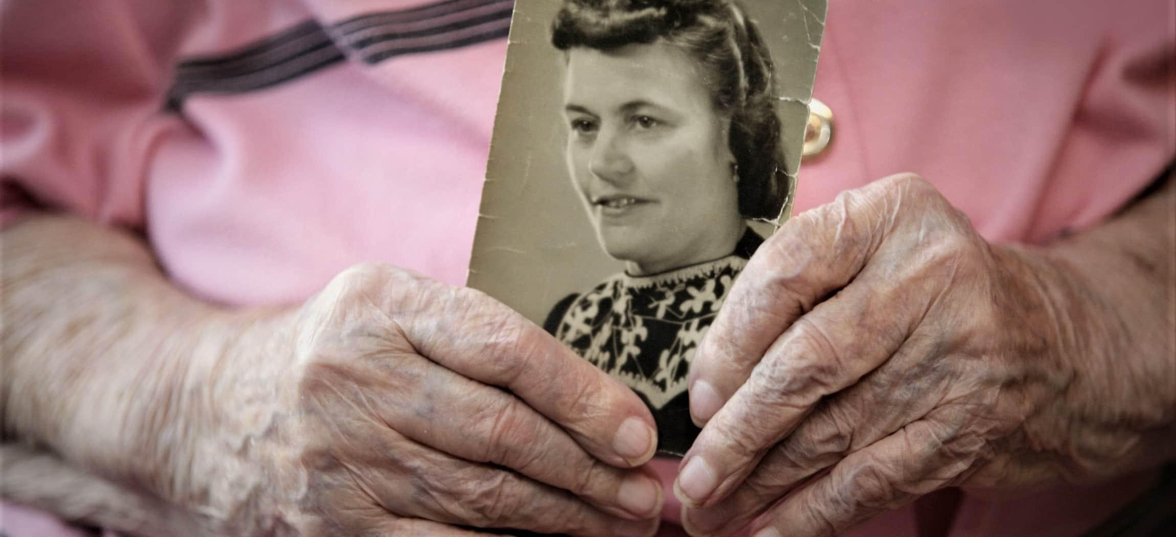 Oude gerimpelde handen houden een klassieke zwart-wit-foto vast, oude vrouw met roze blouse