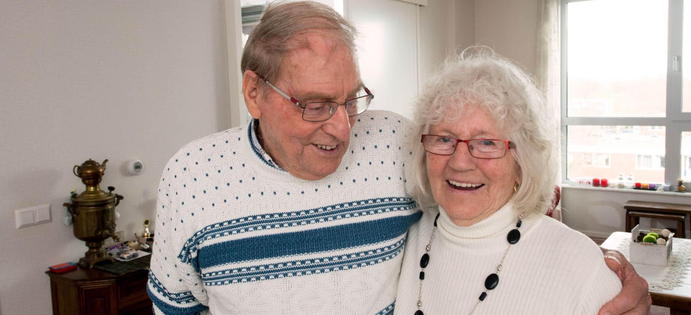Gelukkig ouder echtpaar, man omarmt zijn vrouw, witte trui