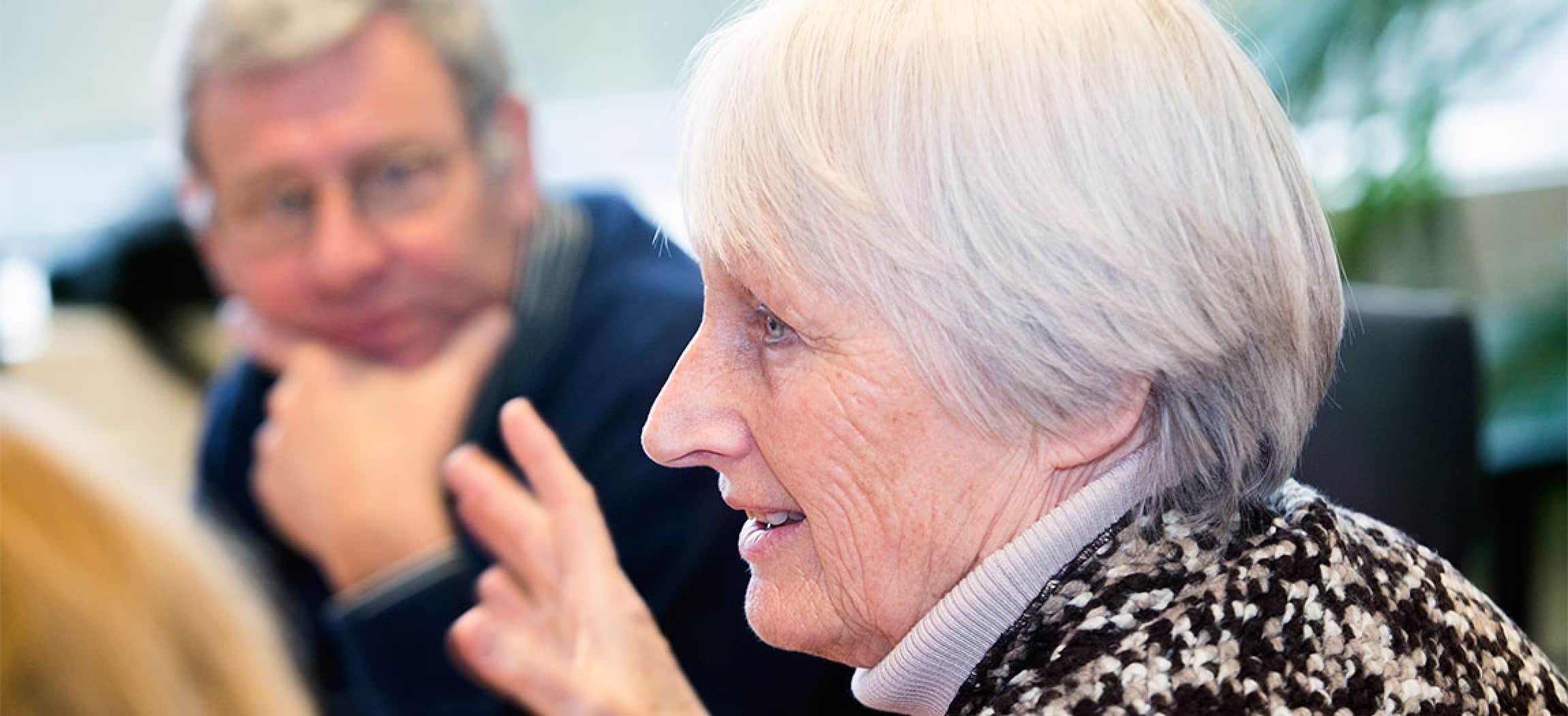 Vergadering vrouw met grijs haar spreekt over serieus onderwerp