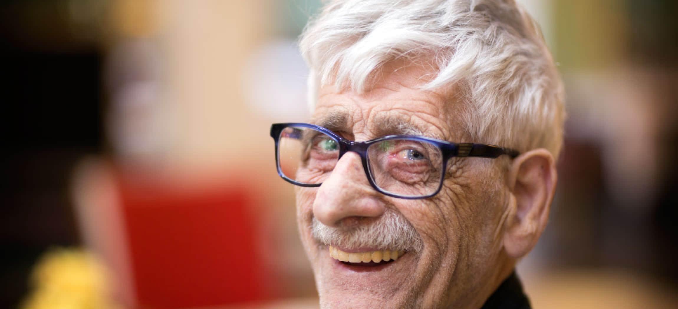 Gerimpelde oude man met grijs pluizig haar en bril kijkt vrolijk om