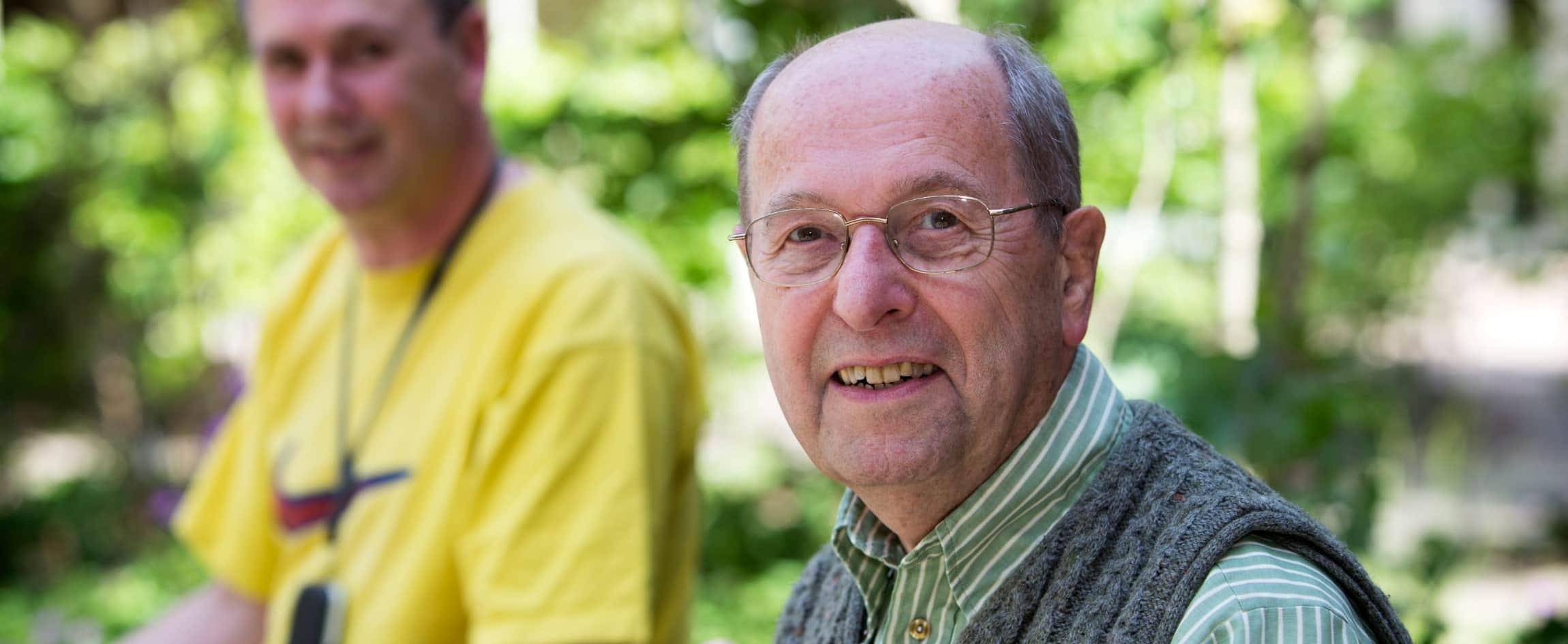 Oudere man met spencer en bril in tuin
