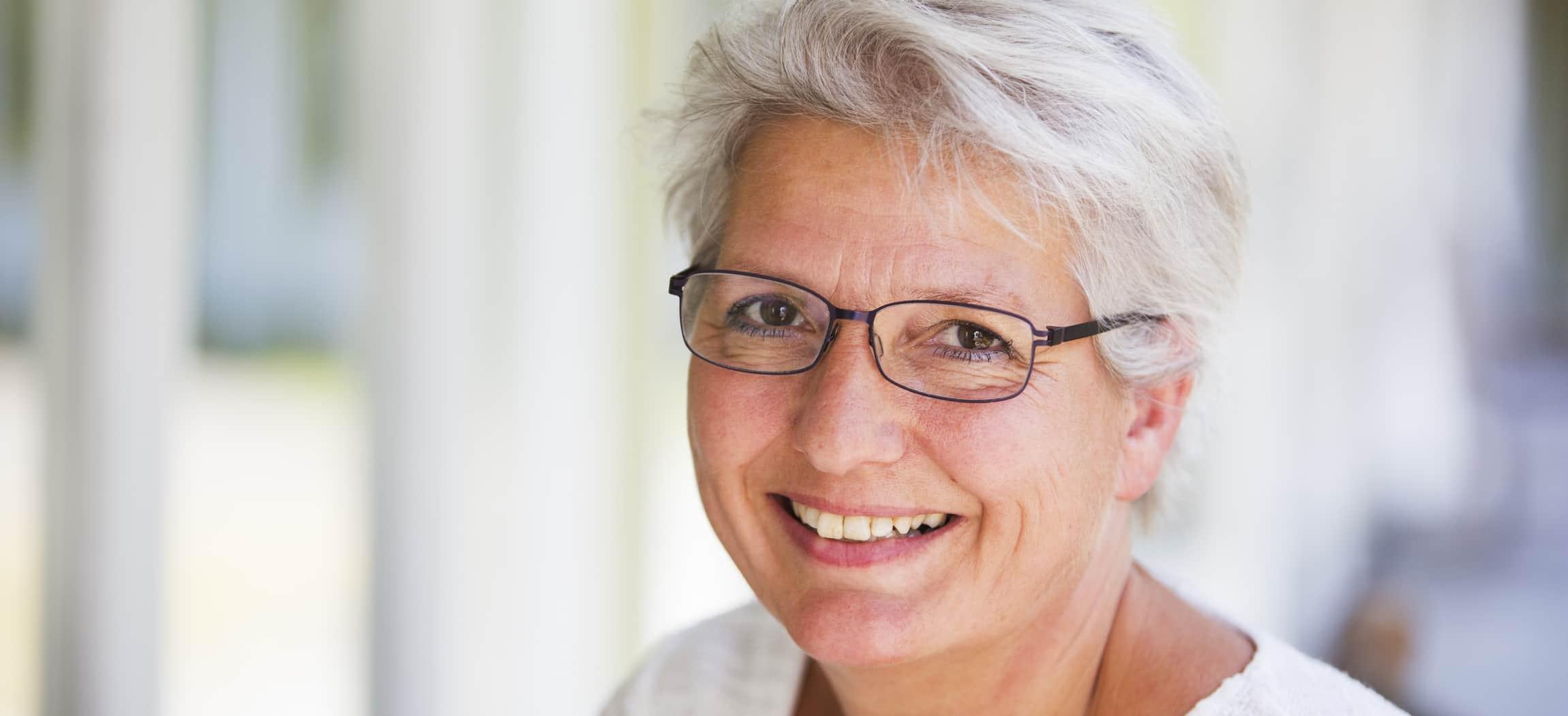 Vrouw zilvergrijs haar, met bril mooie tanden witte achtergrond