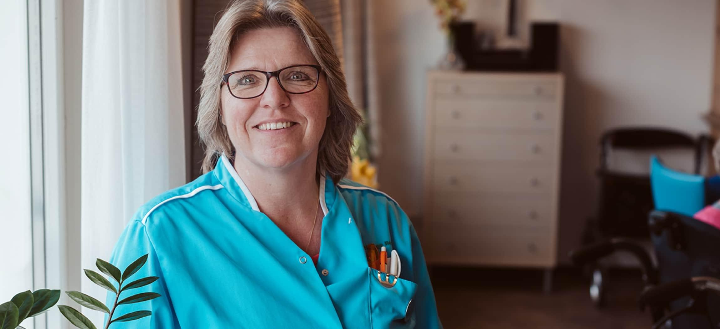Verzorgende in de ouderenzorg met blauw uniformjasje en blond haar (Petra van Lingen)