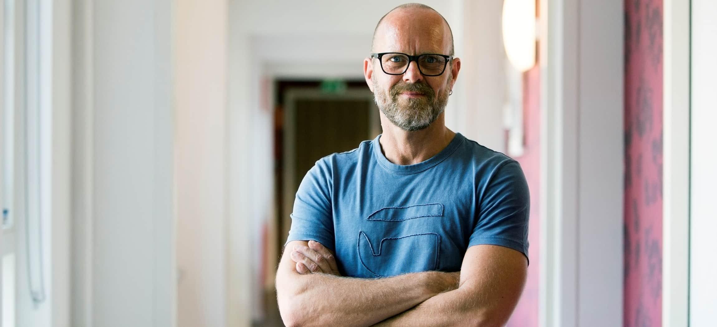 Man in blauw t-shirt met bril staat in een gang met roze behang