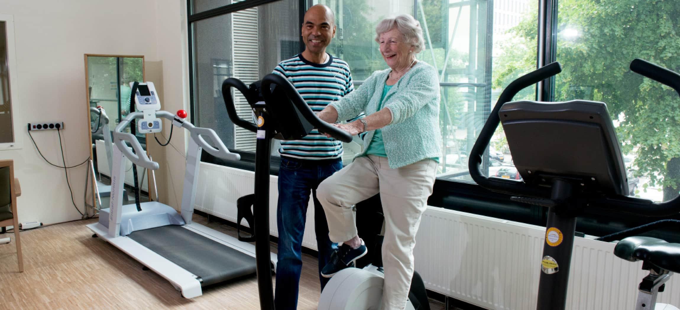 Ergotherapie oefenzaal fitness fiets oude vrouw met fysiotherapeut man