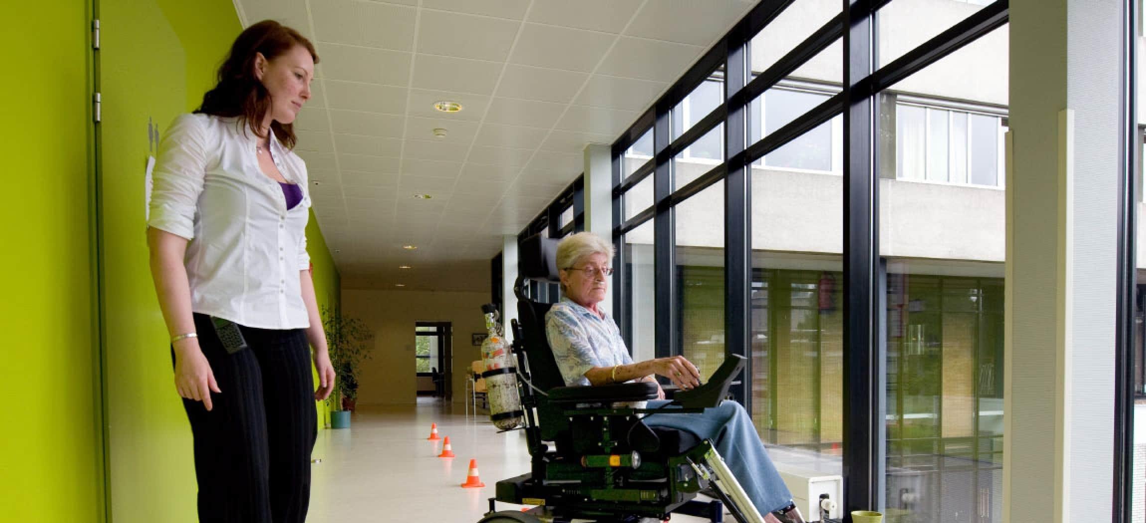 Vrouw in elektrische rolstoel oefent in lange gang met pylon pilon met ergotherapeut