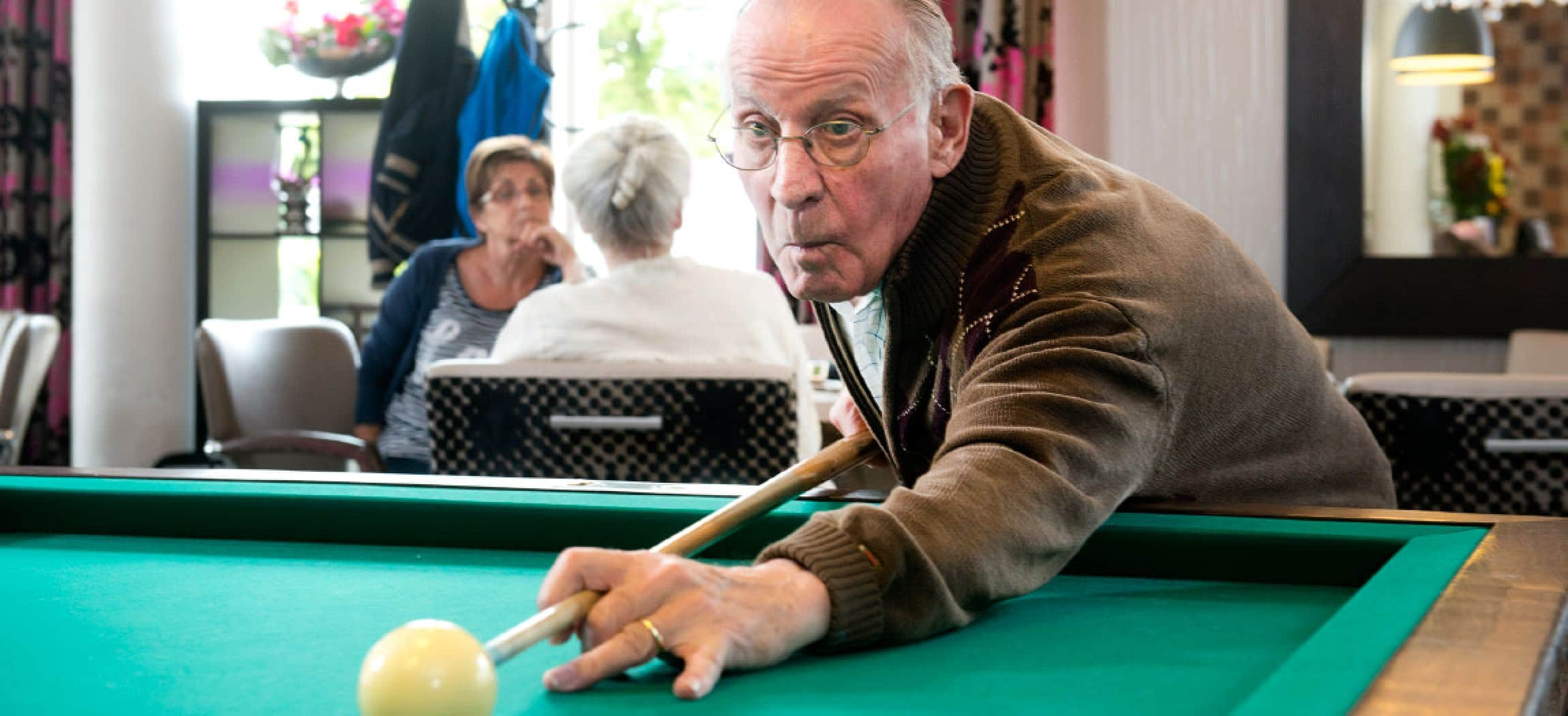 Oudere man bij biljarttafel met biljartkeu en biljartbal