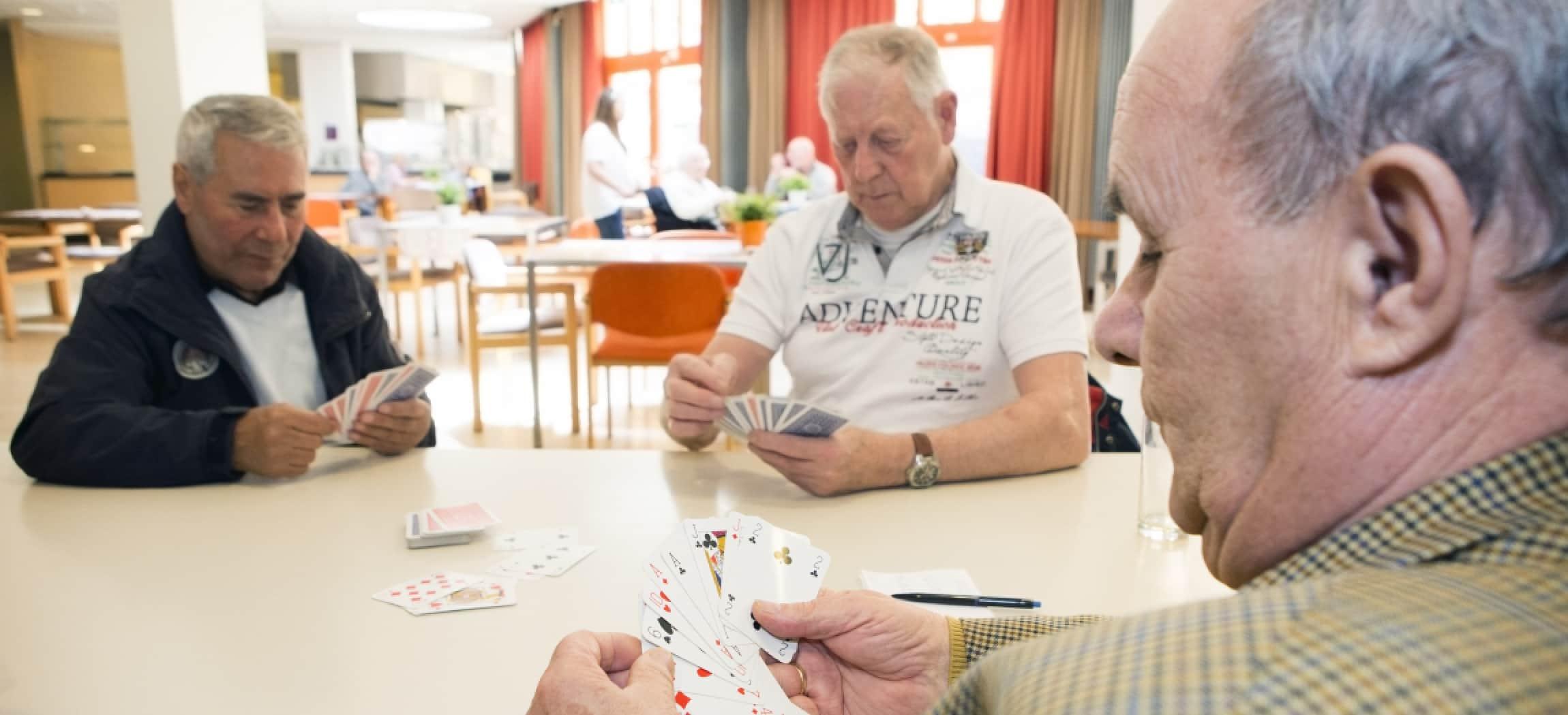 Drie mannen senioren spelen een kaartspel