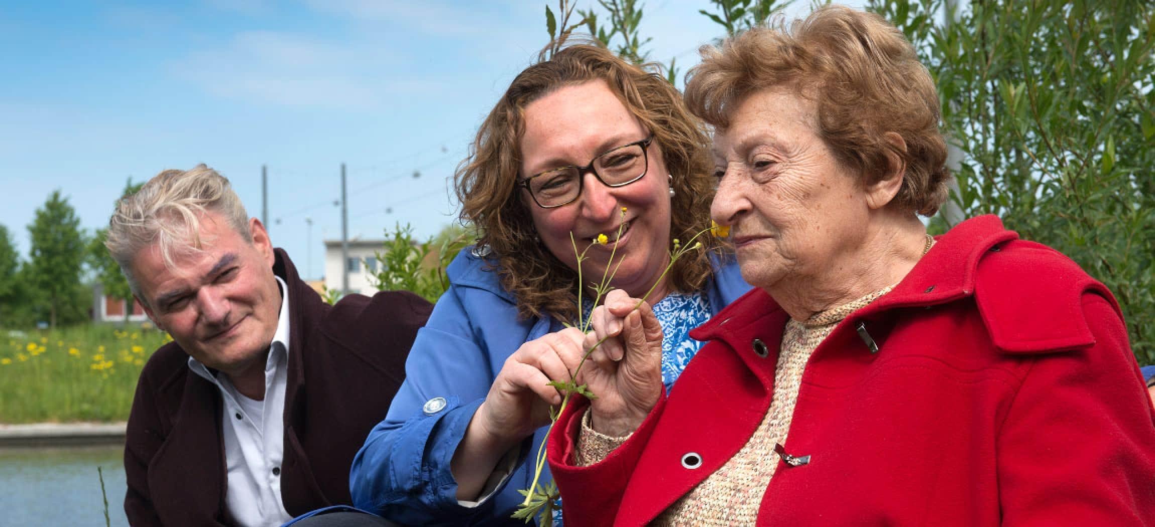 Zonnige dag buiten oudere vrouw met rode jas ruikt aan bloem en man kijkt toe