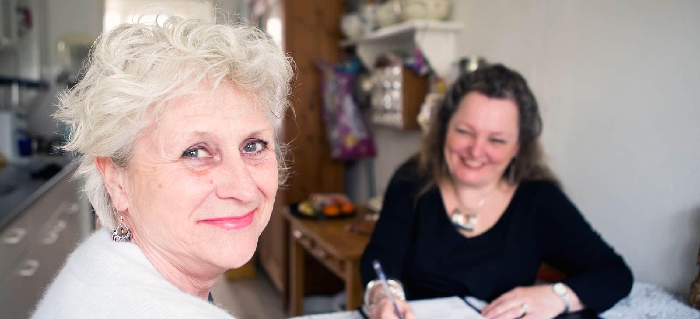Mooie oudere vrouw zit met thuisbegeleider in haar keukentje