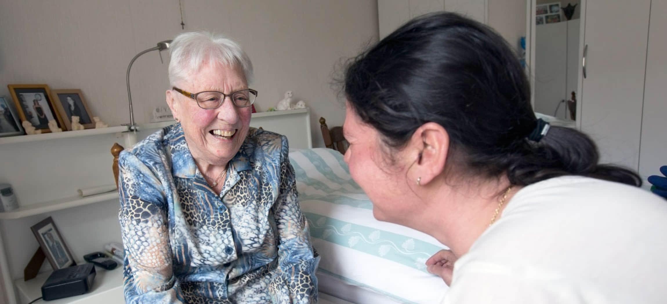 In slaapkamer van oudere vrouw kijkt wijkverpleegkundige oude vrouw aan