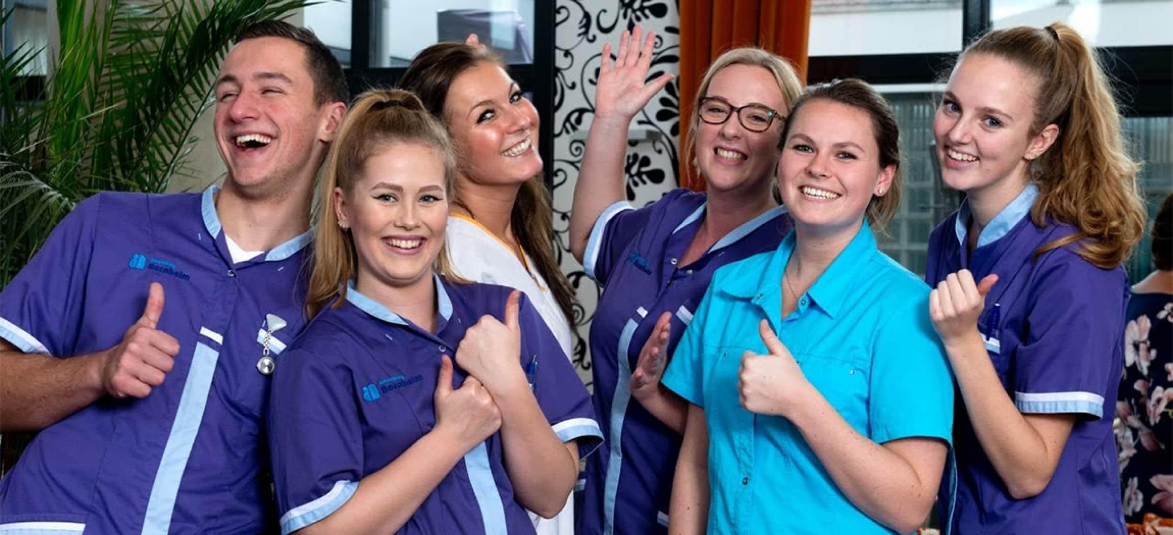 Een team van jonge vrolijke verzorgende in blauw uniform met duim omhoog, tumbs up