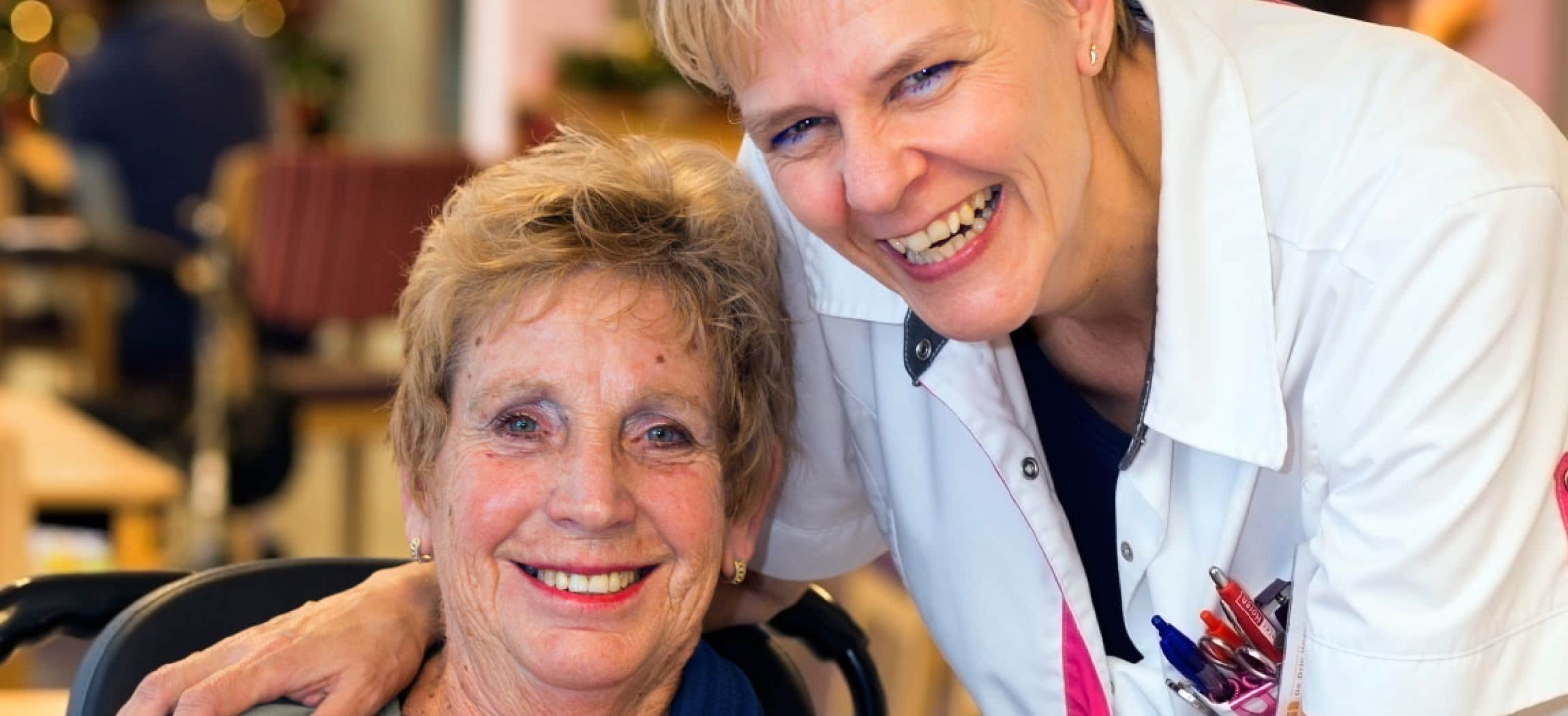 Lachende verpleegkundige omarmt oudere vrouw