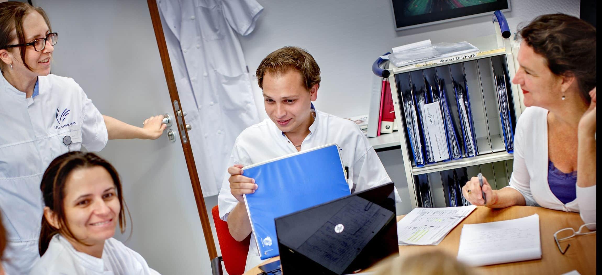 Vier verpleegkundigen in overleg aan tafel met laptop en administratie mappen