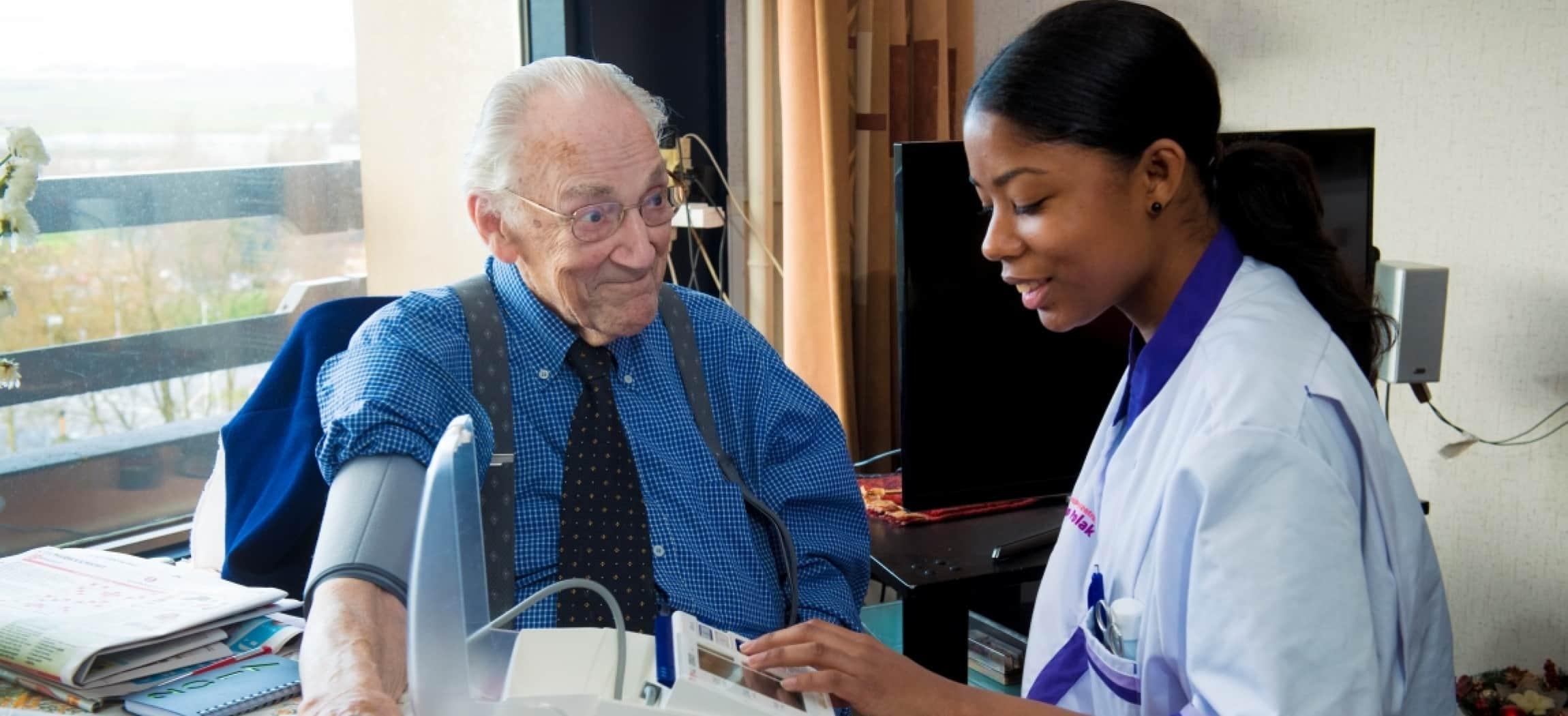 Verpleegkundige met getinte huidskleur neemt de bloeddruk op bij bejaarde man in overhemd en stropdas