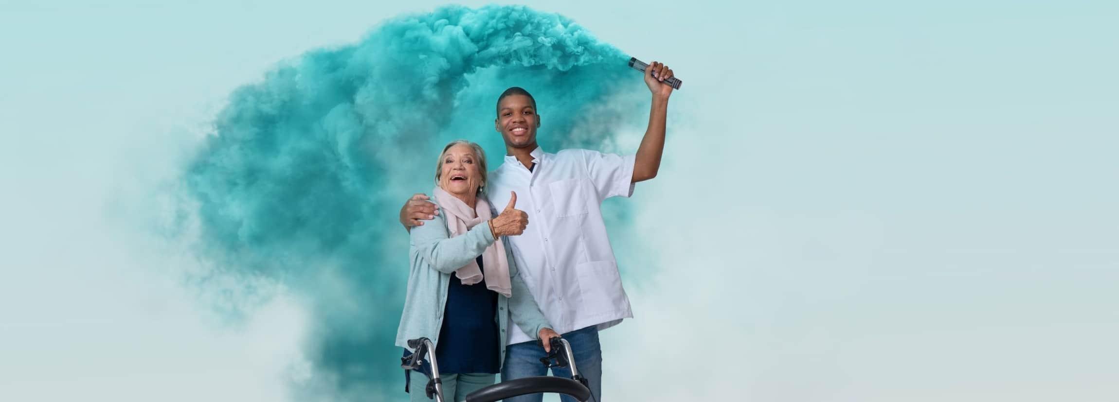 Mannelijke verzorgende met getinte huidskleur omarmt een oudere vrouw en houdt fakkel blauwe rook vast