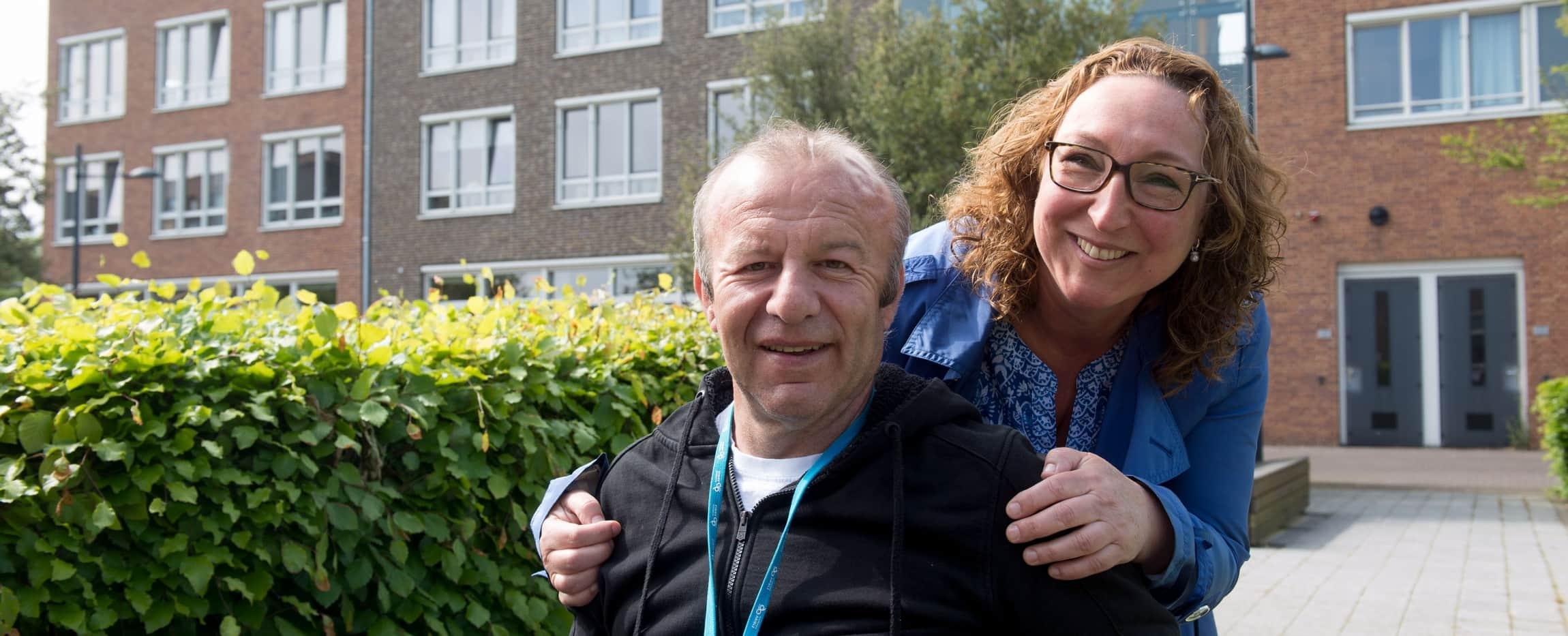 Man in rolstoel met jonge vrouw bij een groene heg en rij huizen