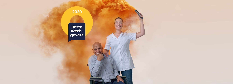 Jonge vrouwelijke verpleegkundige met lachende man in rolstoel houdt fakkel in hand met oranje rookpluim