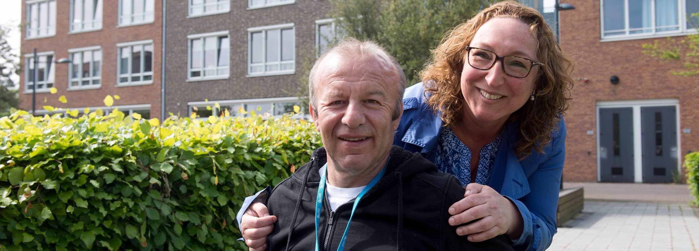 Aardige jonge vrouw omarmt oudere man in rolstoel op de stoep bij een verpleeghuis
